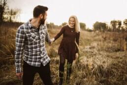 Ein Mann hält seine Partnerin bei einem Shooting bei Sonnenuntergang an der Hand.