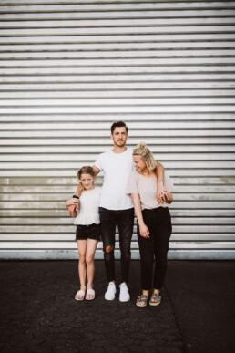 Nadja Morales fotografiert Vater, Mutter und Tochter vor einem großen Tor.