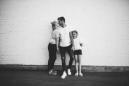 Vater und Mutter geben sich einen Kuss und halten ihre Tochter an der Hand.