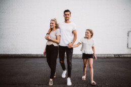 Nadja Morales fotografiert eine Familie auf der Straße vor einer weißen Wand.
