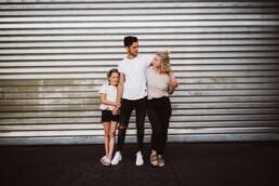 Vater, Mutter und Tochter werden von Nadja Morales vor einem großen Industrietor fotografiert.