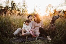 Nadja Morales fotografiert eine junge Familie bei Sonnenuntergang in einer Wiese.