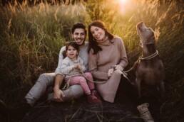 Nadja Morales fotografiert eine Familie, die zum Sonnenuntergang in einer Wiese sitzt.