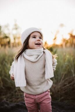 Ein kleines Mädchen lächelt zufrieden.