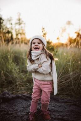 Nadja Morales fotografiert ein kleines Mädchen, das in die Kamera strahlt.
