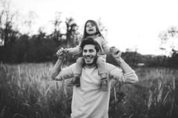 Ein Vater trägt bei einem Fotoshooting seine Tochter auf seinen Schultern und beide lachen in die Kamera.