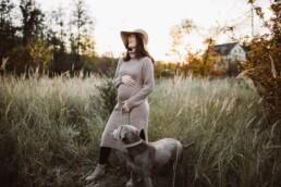 Nadja Morales fotografiert eine werdende Mama mit ihrem Hund zum Sonnenuntergang in der Natur.