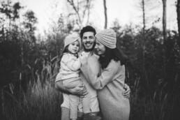 Vater, Mutter und Tochter halten einander bei einem Fotoshooting und lachen gemeinsam.