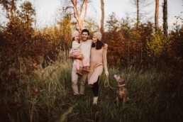 Nadja Morales fotografiert eine Vater, Mutter und Tochter zusammen mit ihrem Hund in der Natur.