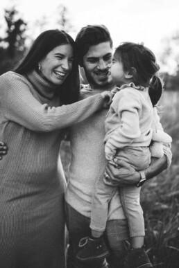 Vater und Mutter lachen bei einem Shooting mit Nadja Morales ihre Tochter an.