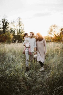 Eine Familie spaziert bei Sonnenuntergang durch eine grüne Wiese.