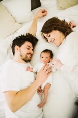 Nadja Morales fotografiert in Ingolstadt eine Homestory, bei der Eltern mit ihrer kleinen Tochter kuscheln.