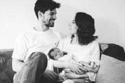 Glückliche, frisch gebackene Eltern lächeln sich an, während sie ihr Baby im Arm halten.