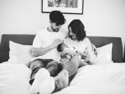 Eine frisch gebackenen Familie kuschelt zusammen im Bett.