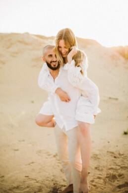 Ein Mann trägt seine Frau bei einem Fotoshooting mit Nadja Morales auf seinem Rücken.