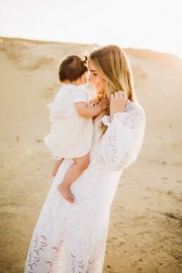 Eine Mutter hält bei einem Fotoshooting mit Nadja Morales glücklich ihre Tochter am Arm.
