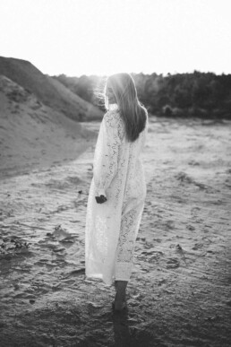 Das Bild zeigt die schwarz- weiß Aufnahme einer jungen Frau im Sonnenuntergang bei Ratingen.