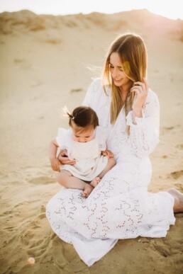 Eine Mutter sitzt bei einem Fotoshooting bei Sonnenuntergang mit ihrer Tochter in einer Kiesgrube.