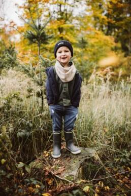 Ein kleiner Junge lacht bei einem Herbstspaziergang bei Ratingen in die Kamera von Nadja Morales.
