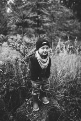 Das Bild zeigt die schwarz-weiß Aufnahme eines kleinen Jungen, fotografiert von Nadja Morales in der Natur bei Ratingen.