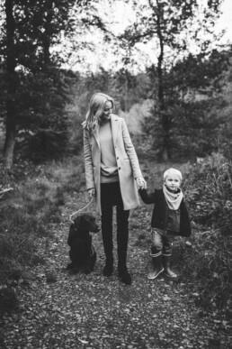 Das Bild zeigt eine schwarz-weiß Aufnahme von Mutter, Sohn und Hund in der Natur bei Ratingen, festgehalten von Nadja Morales.