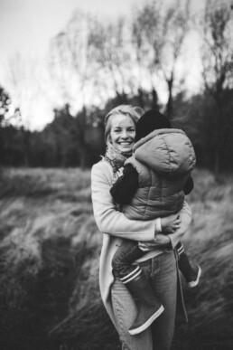 Nadja Morales fotografiert eine Mama. die ihren Sohn trägt und in die Kamera lächelt.