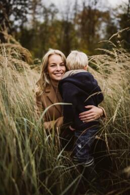 Ein kleiner Junge umarmt seine Mama, die glücklich in die Kamera von Fotografin Nadja Morales lächelt.