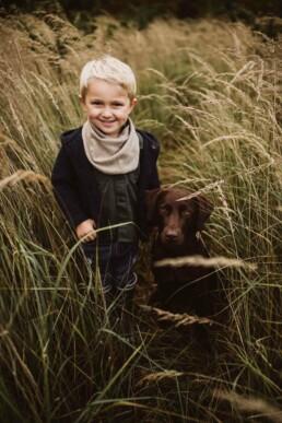 Ein kleiner Junge und sein Hund stehen nebeneinander in einer Wiese.