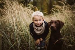 Nadja Morales fotografiert einen kleinen, blonden Jungen zusammen mit seinem Hund.
