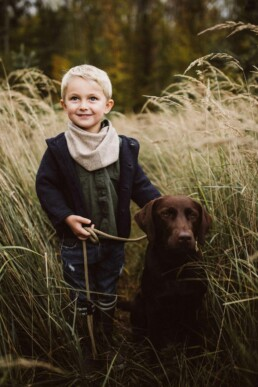 Ein kleiner, blonder Junge lächelt stolz in die Kamera, während er den Hund der Familie an der Leine hält.