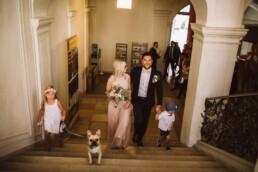 Frisch verheiratetes Brautpaar kommt mit Kindern und Hund eine Treppe hoch.