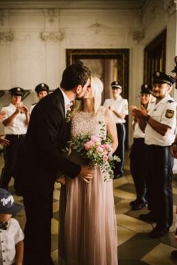 Nadja Morales fotografiert wie ein frisch vermähltes Brautpaar sich küsst.