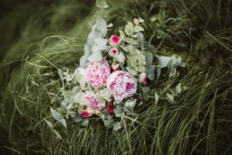 Nadja Morales fotografiert einen Brautstrauß in einer grünen Wiese im Detail.