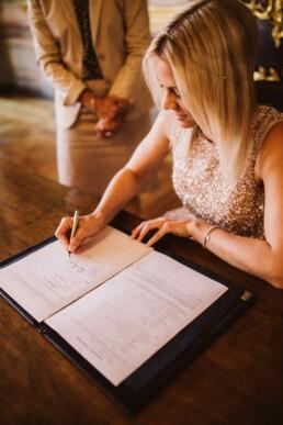 Nadja Morales hält fest, wie die Braut die Eheurkunde unterschreibt.