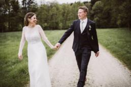 Brautpaar aus München geht beim Fotoshooting mit Nadja Morales Hand in Hand.