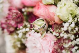 Nadja Morales fotografiert Detailaufnahmen goldener Eheringe an einem Brautstrauß.