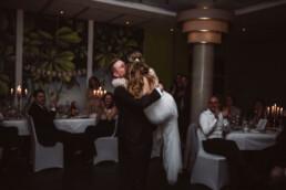 Der Bräutigam trägt seine Frau auf ihrer Hochzeit in München auf Händen.
