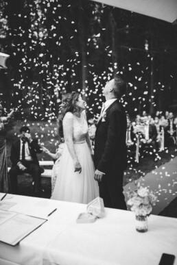 Nadja Morales fotografiert frisch vermähltes Brautpaar aus München, dass mit Konfettiregen überschüttet wird.